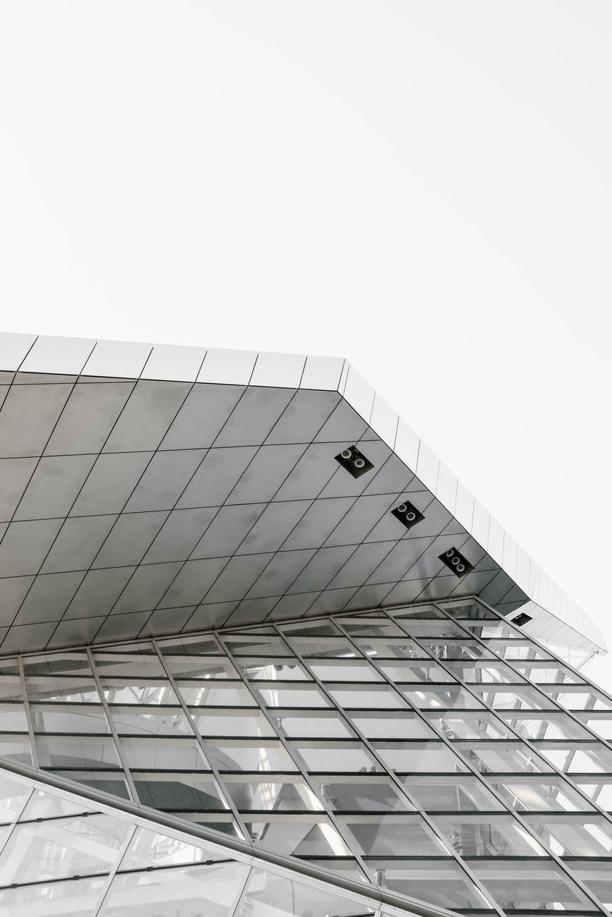 low angle shot of a modern glass building in black and white