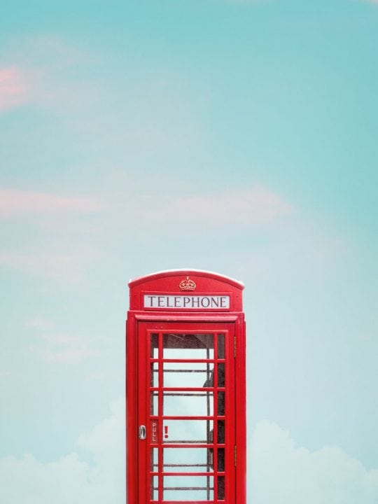 photo of red telephone booth under blue sky
