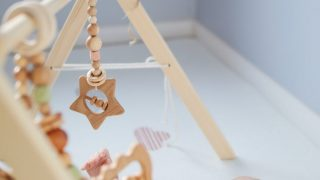 cute toddler playing with wooden rattle