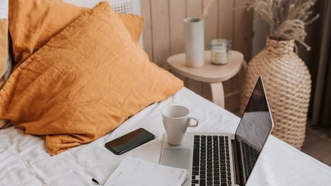 laptop with copybook and cup of coffee on bed sheet