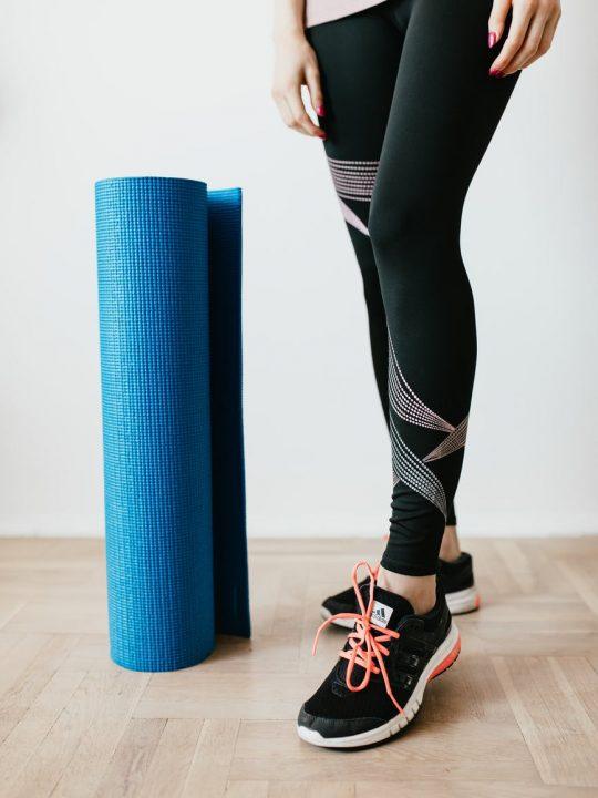 crop sportswoman with fitness mat