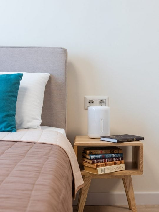 cozy bed and wooden bedside table with stack of books in modern apartment
