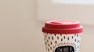 coffee to go with ornament and inscription on table indoors