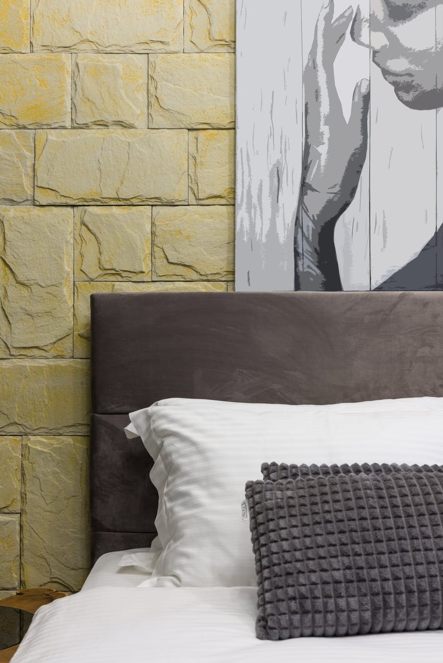 bed with decorative cushions under painting in house