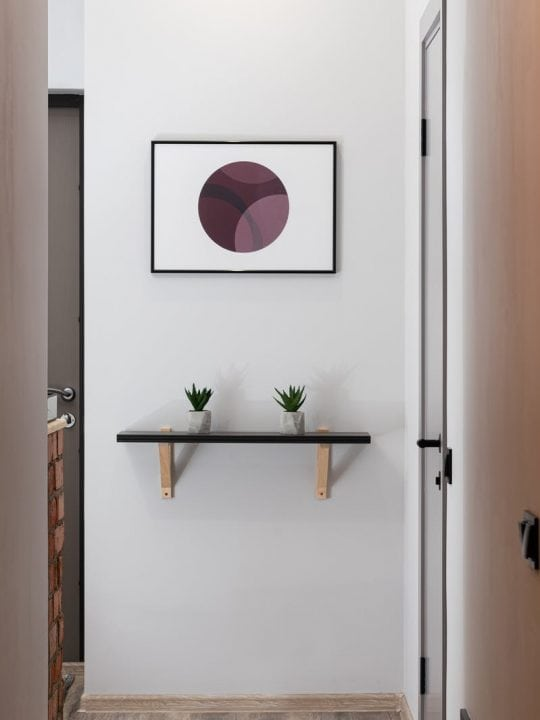 white wall with shelf and abstract painting