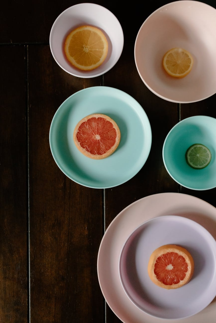 slices of assorted citruses placed in multicolored plates and bowls