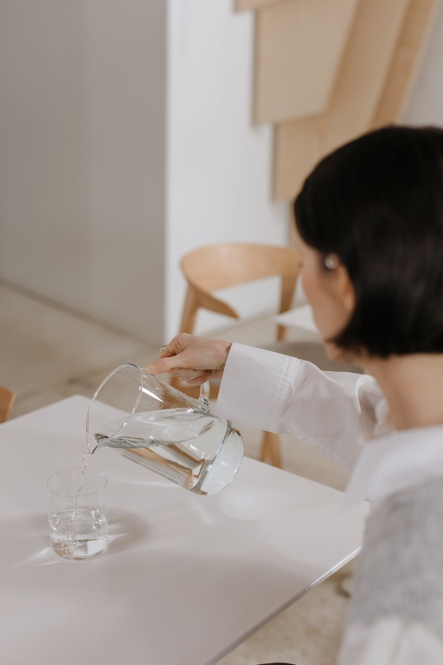 a woman pouring drinking water in a glass