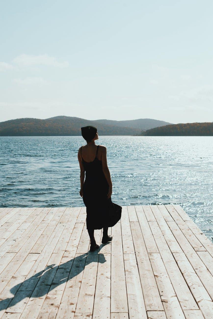 woman in black dress standing on deck near the beach